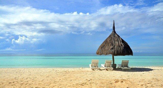 Three beach chairs under an umbrella