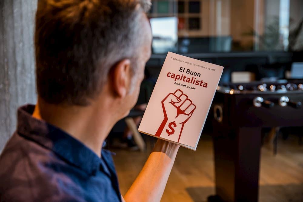"""Imagen de José Carlos León mirando una copia de su libro """"El buen capitalista"""""""